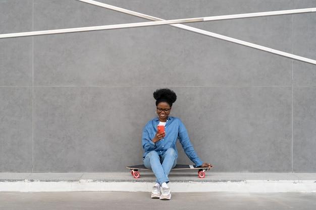Message de type fille noire heureuse dans un smartphone ou faites défiler les médias sociaux via internet g assis à l'extérieur