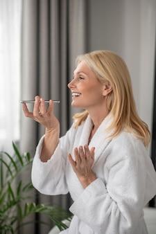 Un message vocal. une femme blonde enregistrant un message vocal et à la recherche de plaisir