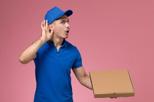 Messager mâle en uniforme bleu tenant la boîte de livraison de nourriture essayant d'entendre sur rose, la prestation de services uniforme de travailleur de l'emploi