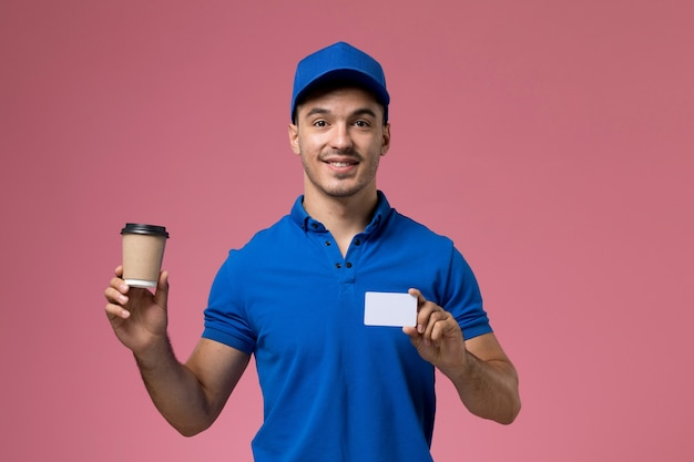 Messager mâle en uniforme bleu tenant la tasse de café de livraison souriant sur rose, prestation de travail de service uniforme