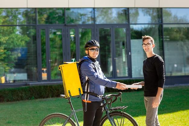 Messager mâle avec vélo et sac thermique donnant une boîte à pizza au client dans la rue près du bureau