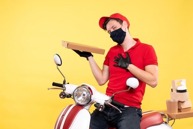 Messager mâle vue de face dans un masque tenant une boîte de nourriture sur jaune