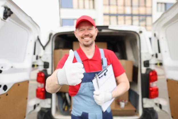 Un messager masculin souriant montre les pouces vers le haut sur fond de voiture avec fret