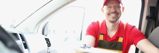 Un messager masculin souriant sort une boîte en carton de la voiture