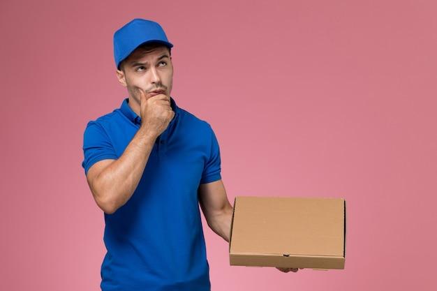 Messager masculin en uniforme bleu tenant la boîte de livraison de nourriture en pensant sur rose, prestation de services uniforme de travailleur de l'emploi