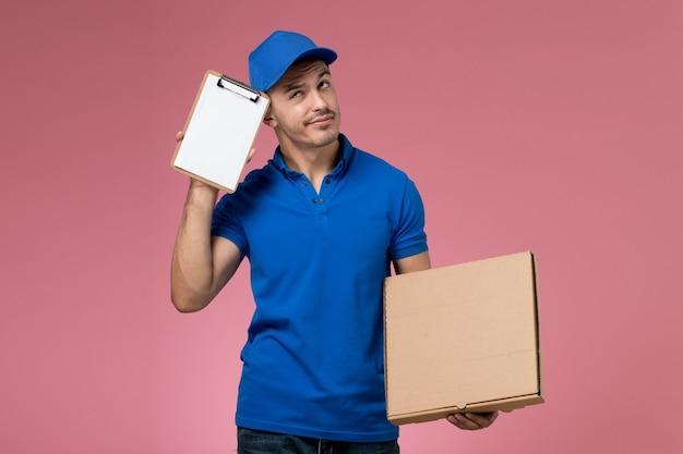 Messager masculin en uniforme bleu tenant la boîte de nourriture de livraison et le bloc-notes sur rose, prestation de services de travail uniforme