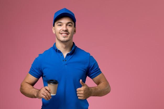 Messager masculin en uniforme bleu tenant une tasse de café et souriant sur rose, prestation de services uniforme de travailleur