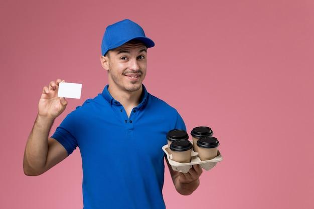Messager masculin en uniforme bleu tenant des tasses de café de livraison et carte sur rose, prestation de services de travail uniforme des travailleurs