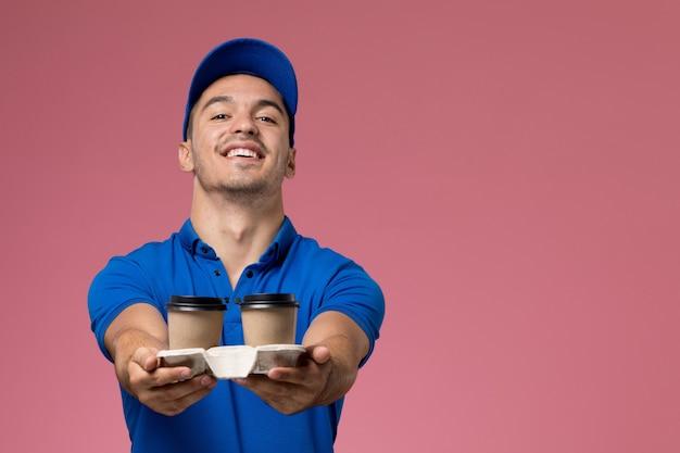 Messager masculin en uniforme bleu tenant des tasses à café se réjouissant de rose, prestation de services uniforme de travailleur de l'emploi