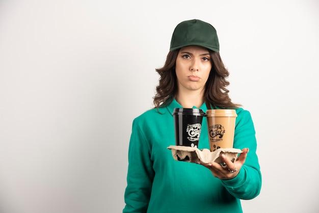 Messager troublé tenant des tasses à café sur blanc.