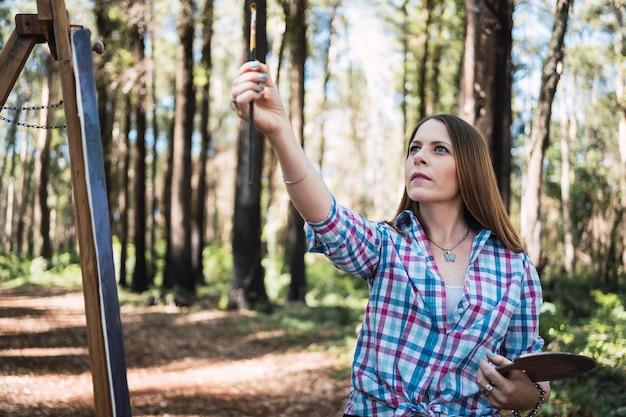 Mesure de l'artiste en peinture femme artiste peint une image à l'extérieur