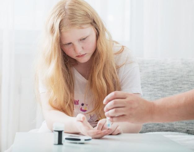 Mesurer la glycémie d'une adolescente avec un glucomètre