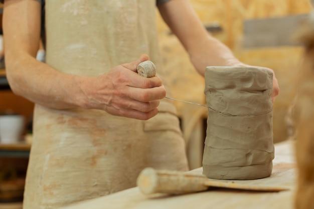 Mesurer la quantité nécessaire. pièce d'argile nécessaire à la coupe précise avec un outil en fil de fer pour des utilisations futures