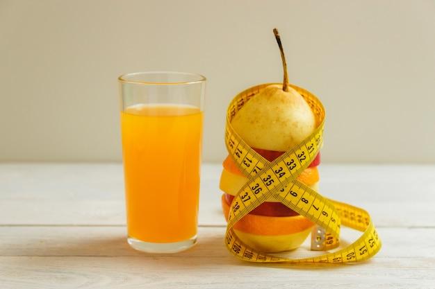 Mesurer le ruban et les fruits frais sur une table en bois. régime de vie sain avec des fruits frais.