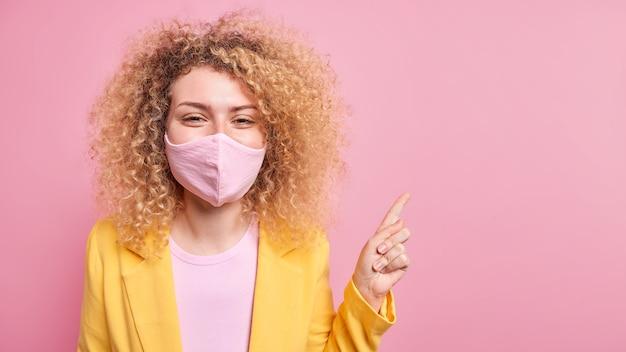 Mesures préventives et concept de soins de santé. heureuse belle femme aux cheveux bouclés se protège du coronavirus porte un masque facial indique à l'espace vide montre votre logo ou texte promotionnel