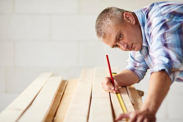 Mesurez le matériau en bois deux fois par le menuisier