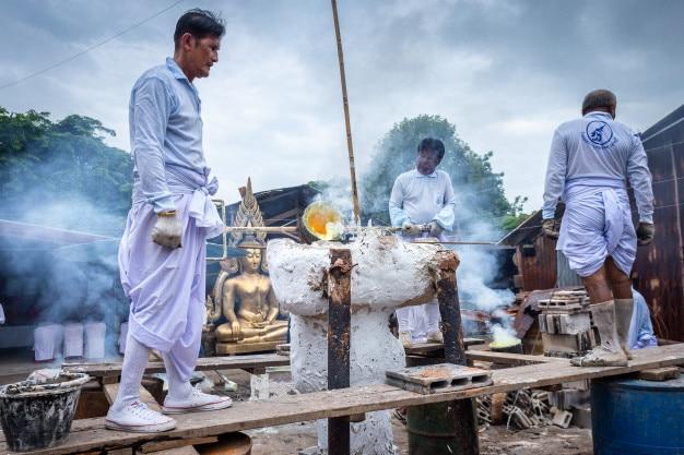 Le métal en fusion est versé dans un moule en aluminium moulé dans le sable et le temple de bouddha en thaïlande