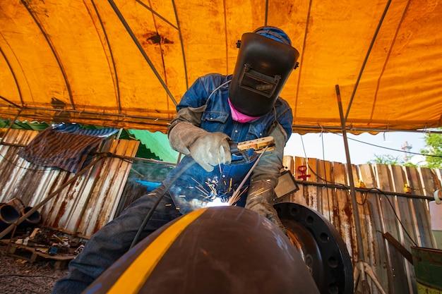 Le métal de travailleur masculin de soudure fait partie de la construction de pipeline de buse de machines, du pétrole et du gaz
