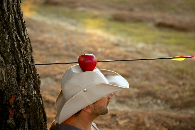 Métaphore de guillaume tell, pomme et flèche en forêt