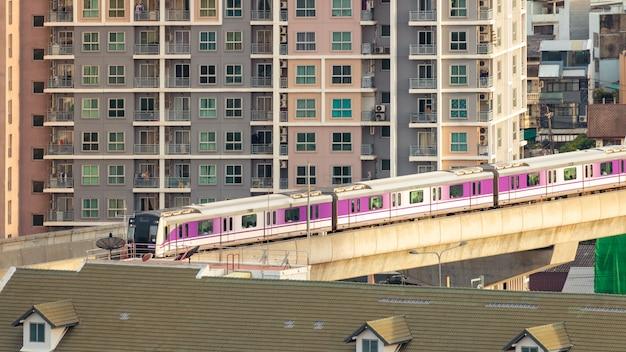 Le métro aérien électrique traverse la ville, les bâtiments et les maisons.