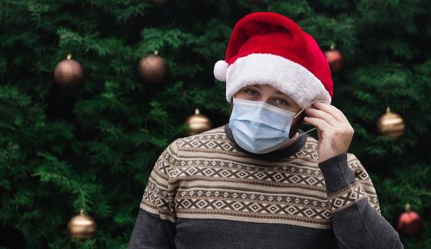 Mettez correctement un masque médical. gros plan portrait d'un homme portant un chapeau de père noël, pull de noël et masque médical avec émotion. dans le contexte d'un arbre de noël. pandémie de coronavirus