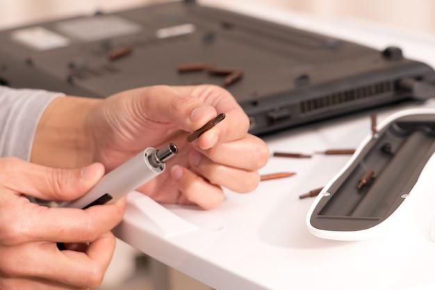 Mettre l'accent sur les femmes tenir le tournevis pour réparer l'ordinateur portable, réparer et entretenir