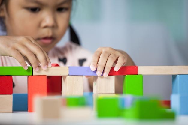 Mettre l'accent sur les mains de la mignonne petite fille jouant avec des blocs de bois colorés dans la chambre