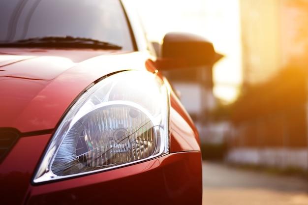 Mettre l'accent sur les phares de la voiture rouge sur la rue avec des fusées éclairantes.