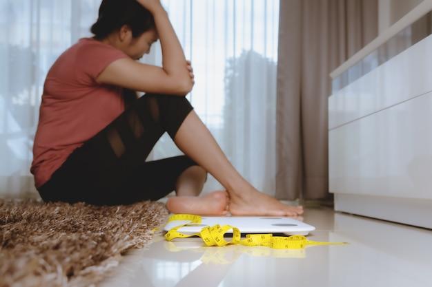 Mettre à l'échelle et mesurer le ruban avec une femme déprimée, frustrée et triste assise sur le sol
