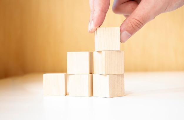 Mettre et empiler à la main des cubes en bois vierges sur une table avec un espace de copie pour le libellé d'entrée et l'icône infographique.