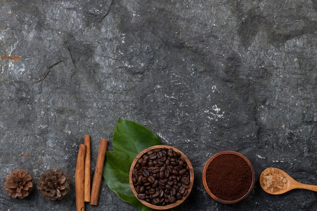 Mettre les grains de café à plat dans une tasse en bois sur une feuille verte, du sucre dans une cuillère en bois, du pin sur une pierre noire