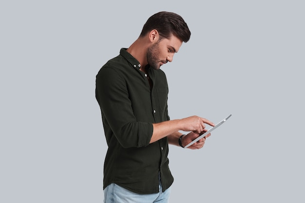 Mettre des idées dans quelque chose de réel. jeune homme sérieux travaillant sur sa tablette numérique en se tenant debout sur fond gris