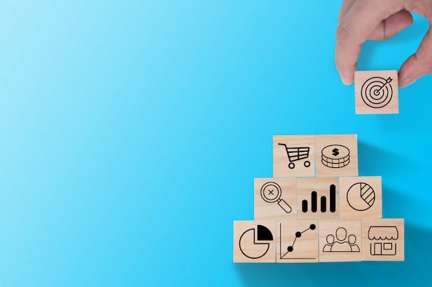 Mettre à la main l'écran d'impression d'icône cible sur un cube en bois pour l'empiler sur une autre icône d'investissement comme un graphique, une pièce d'un dollar et un chariot. concept d'investissement commercial.