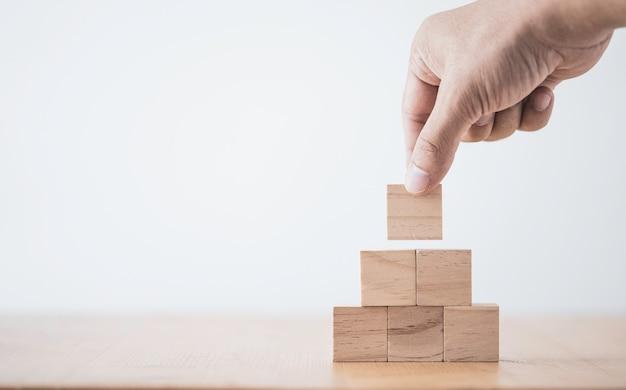 Mettre à la main et empiler des cubes en bois vierges sur table avec espace de copie pour le texte d'entrée et l'icône infographique.