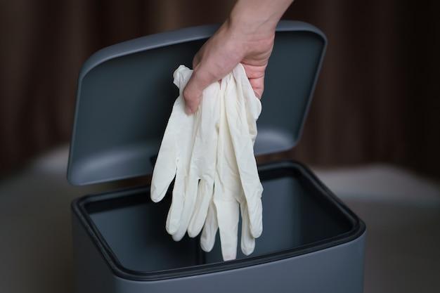 Mettre à la main des gants chirurgicaux sales dans une poubelle.