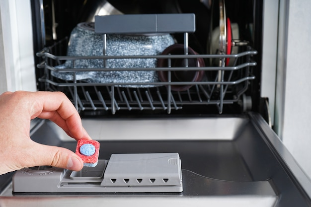 Mettre l'onglet dans le lave-vaisselle, gros plan. une main d'homme tenant une tablette de détergent pour lave-vaisselle.