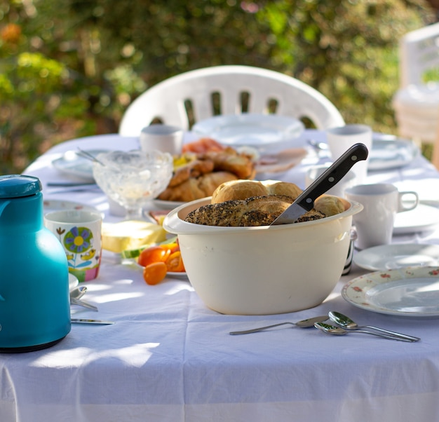 Mettre la table dans la nature. nappe blanche. fête de jardin décontractée en plein air au printemps ou en été pour le déjeuner-dîner.