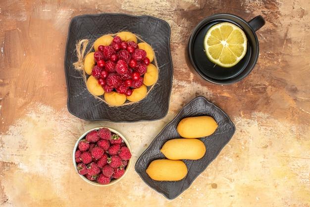 Mettre la table avec un gâteau cadeau et une tasse de thé au citron sur des images de table de couleurs mélangées