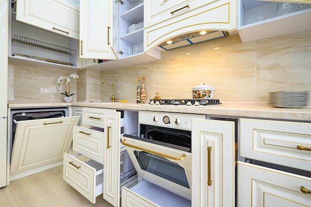 Meubles beige à la cuisine avec toutes les portes ouvertes