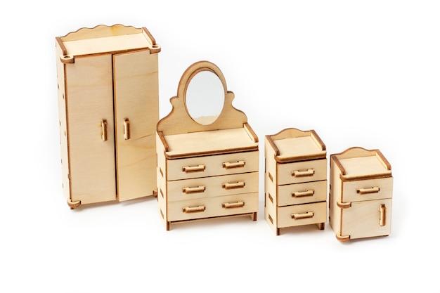 Meubles de chambre en bois miniature jouet se dresse sur un fond blanc. armoire, table de chevet et commode. meubles pour poupées et maison de poupée.