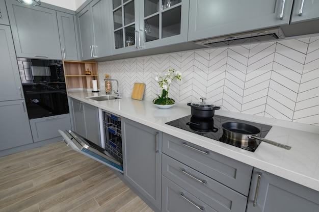 Meubles de cuisine modernes gris et blancs à la mode avec porte de fours ouverte