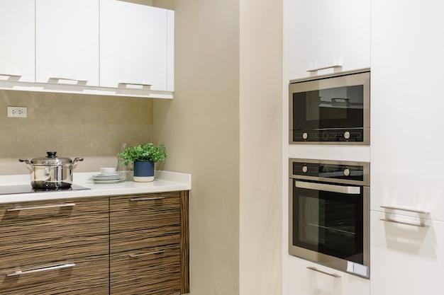 Meubles de cuisine modernes avec ustensiles de cuisine contemporains comme la hotte, cuisinière à induction noire