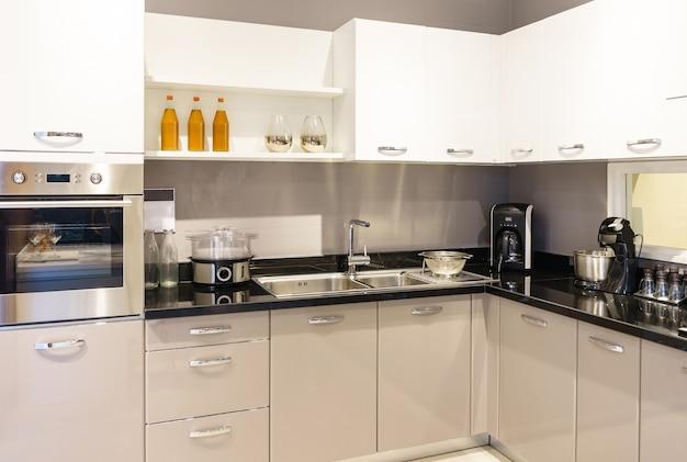 Meubles de cuisine avec ustensiles de cuisine contemporains comme la hotte