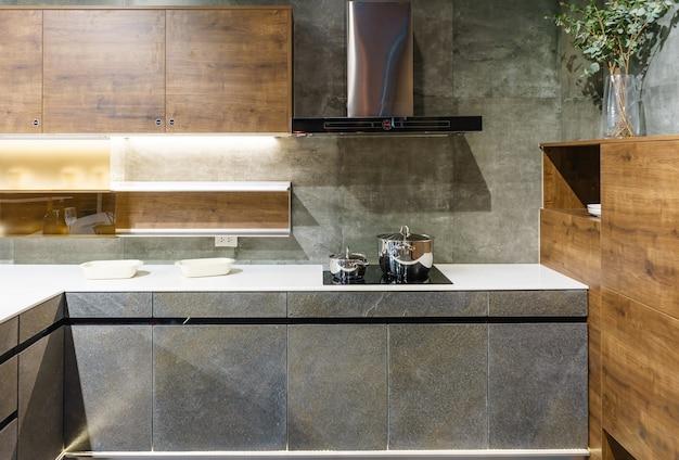 Meubles de cuisine avec ustensiles de cuisine contemporains tels que hotte, cuisinière à induction noire et four