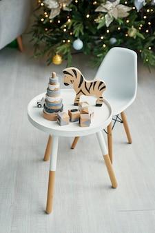 Meubles pour enfants scandinaves. chambre d'enfant scandinave avec sapin de noël, table, chaise et jouets éducatifs en bois. l'intérieur de la chambre des enfants dans le style loft.