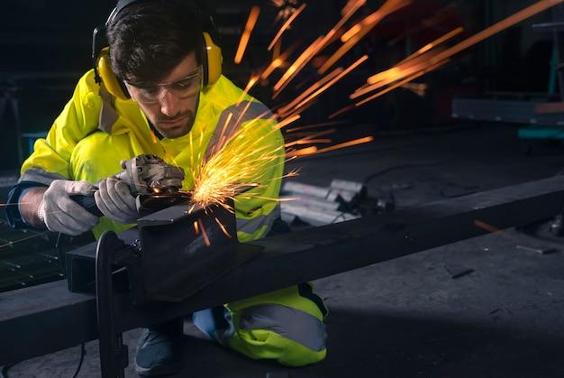 Meulage de roue électrique sur structure en acier en usine, cette image peut être utilisée pour le concept industriel, des travailleurs et de la sécurité