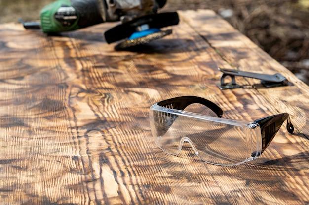 Meule en bois poli, meule abrasive et lunettes de sécurité. texte libre, espace de copie,