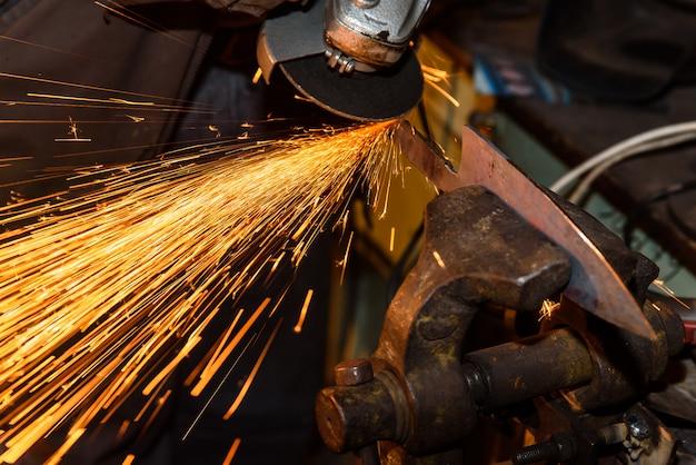 Meuler des outils en métal avec des étincelles - atelier de forge
