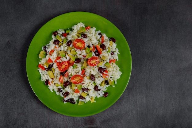 Mexicain fait maison avec du riz, des haricots, du maïs, des tomates, un bol à salade d'avocat