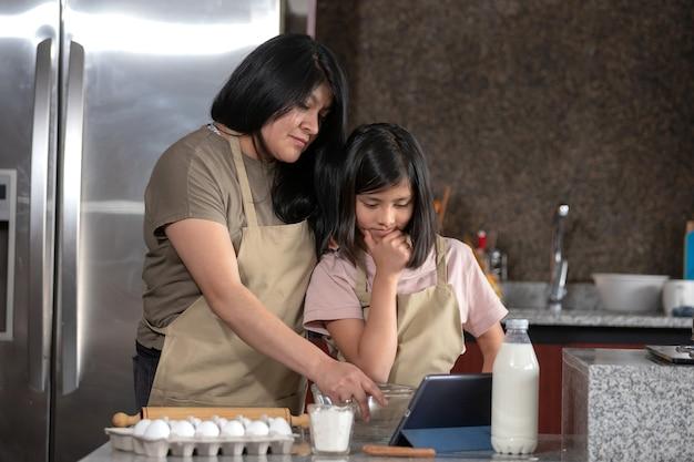 Mexicaine mère et fille cuisine dans la cuisine à la recherche de la recette sur une tablette